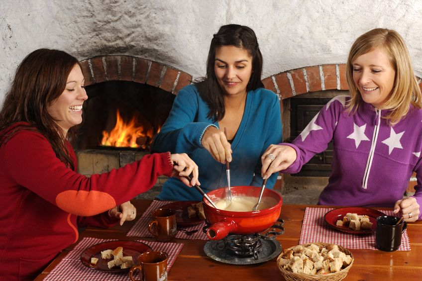 photo of three beautiful females dipping bread into the melted cheese in a fondue pot.