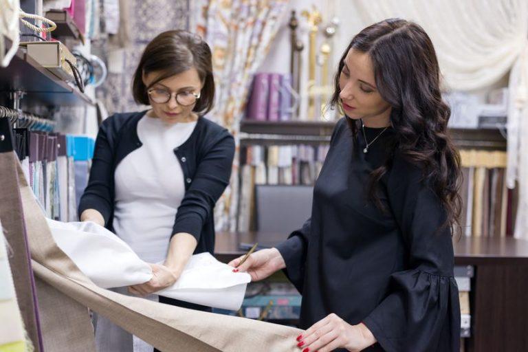 uma mulher mostrando a colcha para o cliente