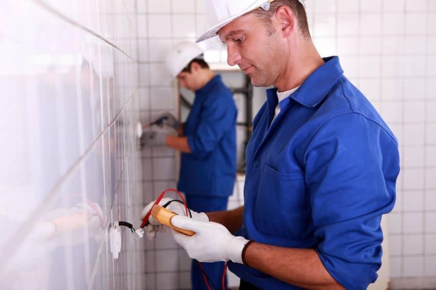 Eletricistas medindo energia com aperímetro.