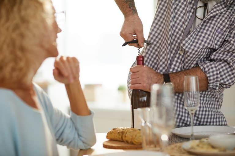 Casal abrindo garrafa de vinho.