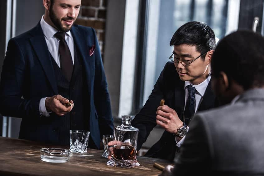 Imagem de homens fumando e bebendo whisky.