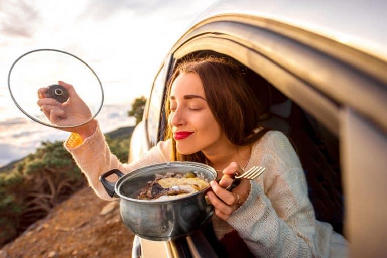 Imagem de mulher dentro de carro segurando panela e tampa em outra mãe e cheirando a comida.