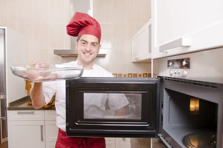 Homem colocando prato no micro-ondas.