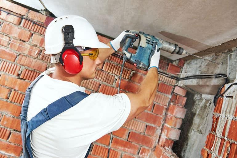 Homem trabalhando em obra com furadeira de impacto.