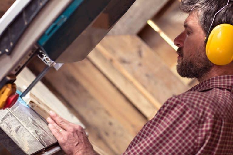 Homem trabalhando com serra fita.
