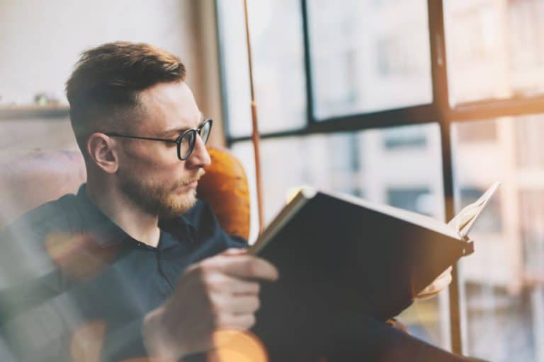 Imagem de homem lendo livro ao lado de janela.