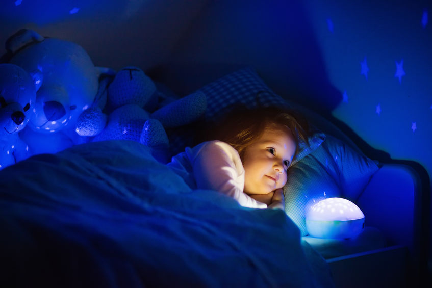 Little girl in bed with night lamp
