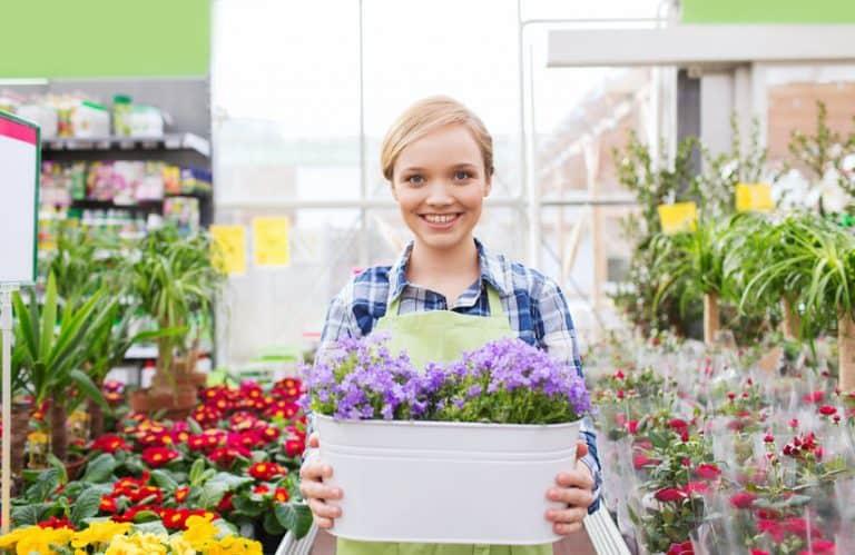 Imagem de mulher segurando cachepot com flores e outras flores em volta.