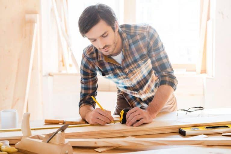 Homem fazendo marcações em tábuas de madeira