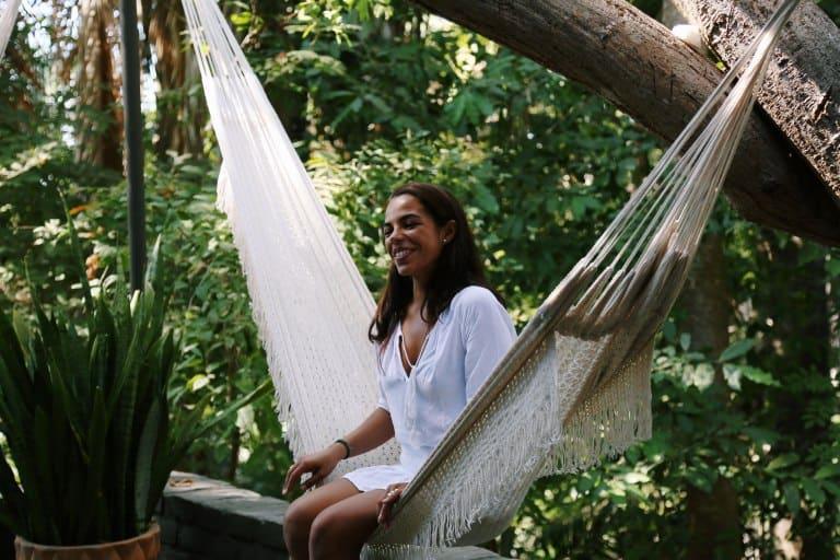 Mulher sentada em rede de descanso em meio a natureza.
