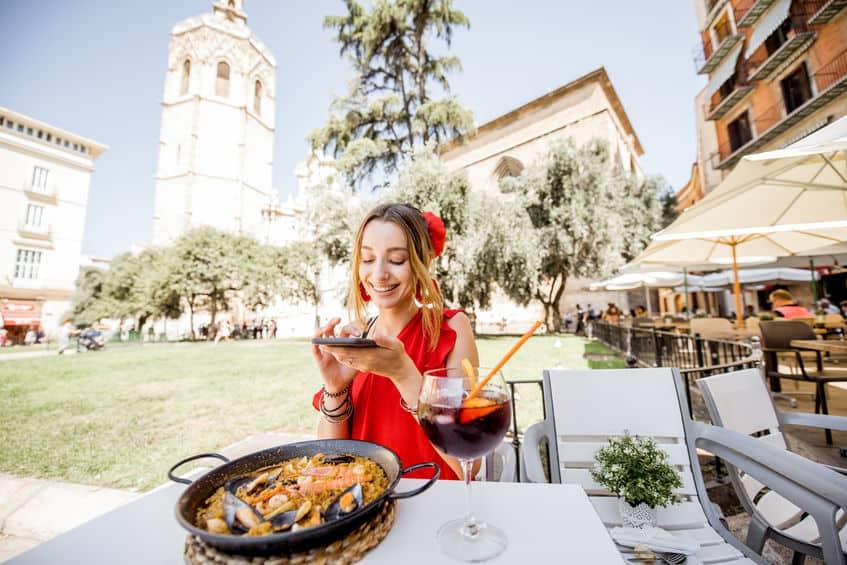 Imagem de mulher tirando foto do seu prato de paella.