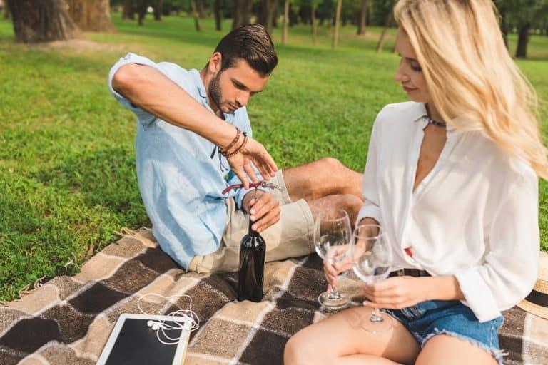 Casal fazendo picnic em parque.