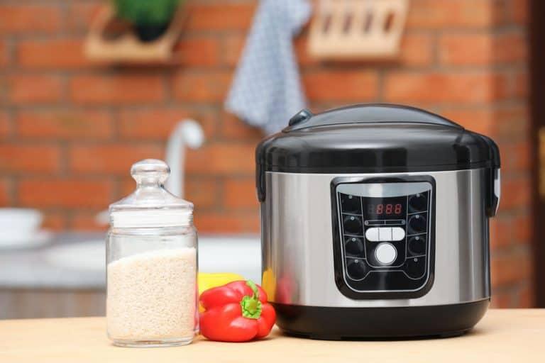 Pote com arroz, pimentão e panela elétrica de arroz sobre bancada.