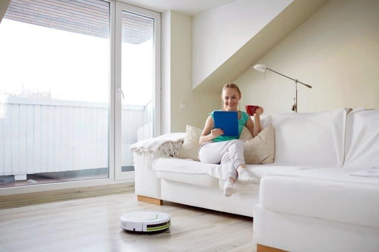 Imagem de mulher em sala de estar com robô aspirador.