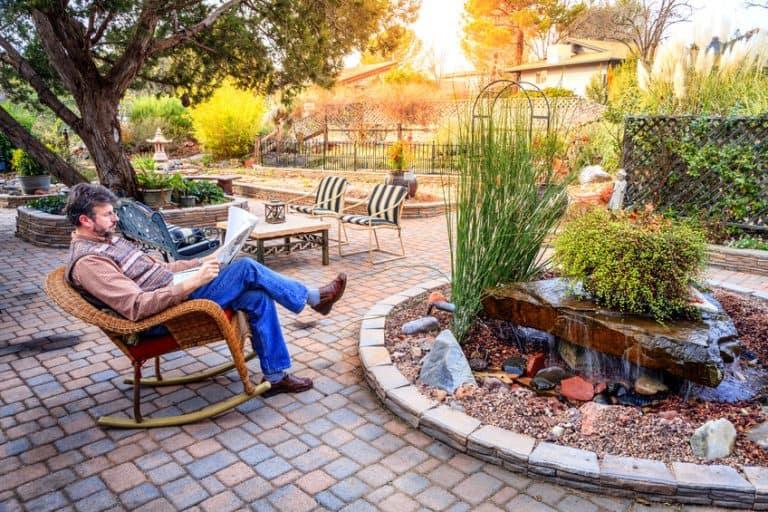 Homem lendo jornal sentado em cadeira de jardim.
