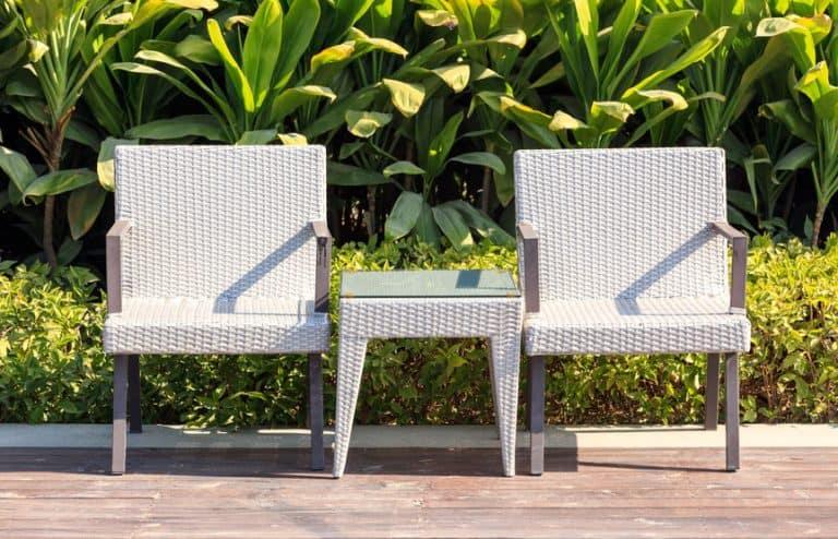 Cadeiras e mesa em jardim.